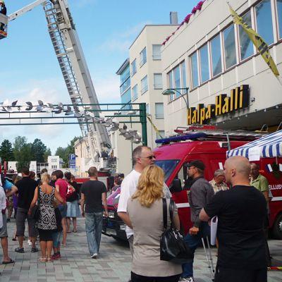 Kuvassa väkeä Pietarsaaren kesäisellä kävelykadulla, taustalla pelastuslaitoksen nosturiauto