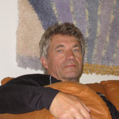 Johan Karjaluoto istuu sohvalla, seinällä miehen itsensä kymmenen vuotta sitten tekemä ryijy.