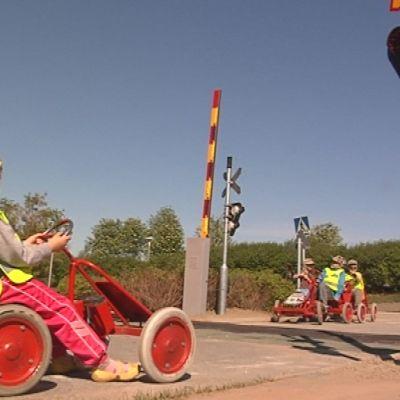 Lapsia odottaa junaa polkuautoissa Luuniemen liikennepuiston tasoristeyksessä.