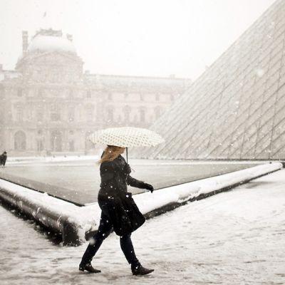 Nainen kävelee Louvren taidemuseon edessä sateenvarjo suojanaan vetisessä lumisateessa.