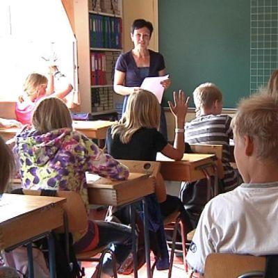 Opetustilanne koululuokassa, oppilaita viittaamassa, opettaja seisoo luokan edessä