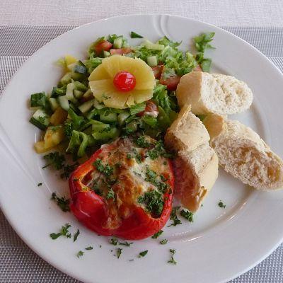 Lautasella aurajuustolla täytetty paprika, vihersalaatti ja patongin paloja.