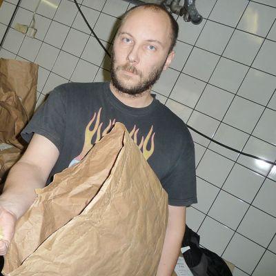 Kuvassa Tomi Karhula pitää kädessään paperisäkistä otettua kuivattua perunaa