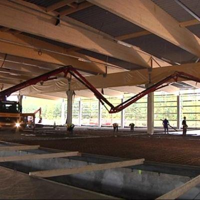 Betoniauto suuressa varastohallissa valamassa lattiaa.