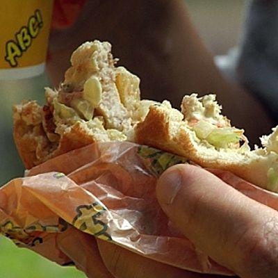 Asiakas syö hampurilaista ABC-huoltoasemaketjun ravintolassa.