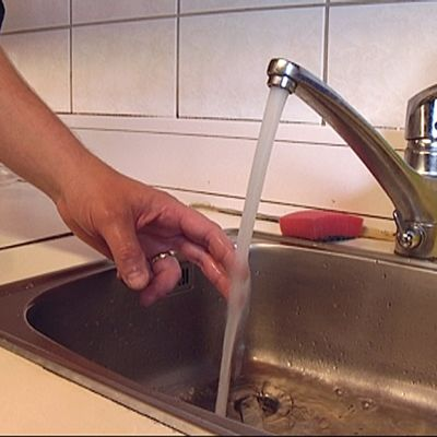 Nainen koettaa sormella hanasta valuvaa vettä