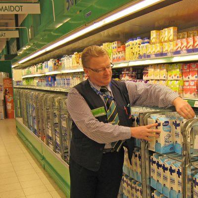 Olli Isoniemi asettelee maitopurkkeja rullakkoon.