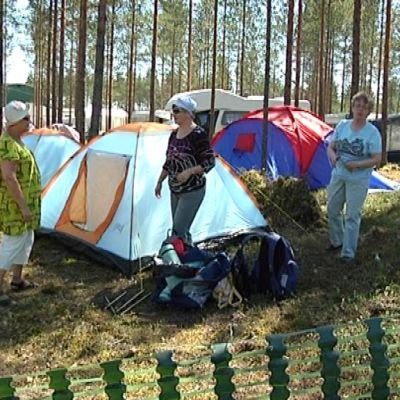 Kolme ihmistä telttailualueella.