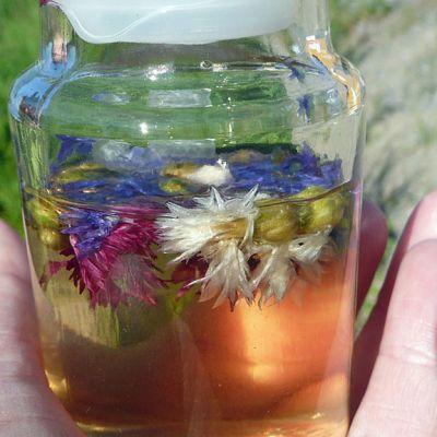 Ruiskaunokeista ja muista kukista tehtyä kasvovettä lasipurkissa