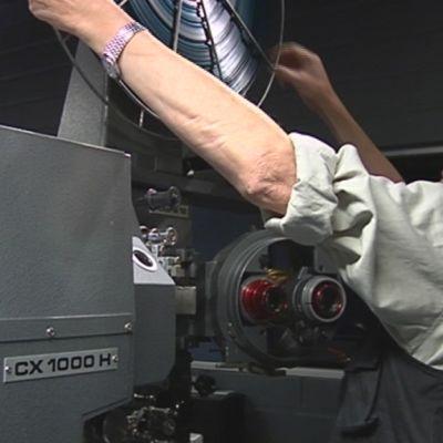 Elokuvateatteri Studion elokuvaprojektoriin asennetaan nauhaa.