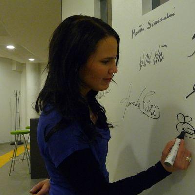 Nainen kirjoittaa nimeään seinään.