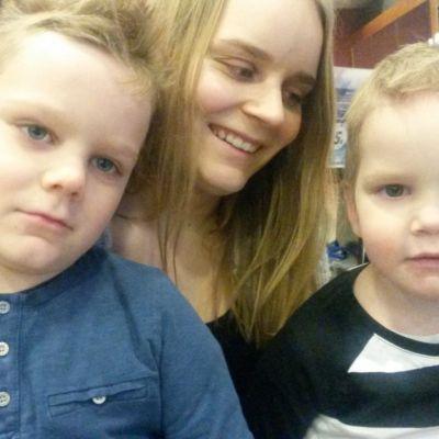 Vaaleahiuksinen nainen istuu kuusen edessä kaksi pientä poikaa sylissään.