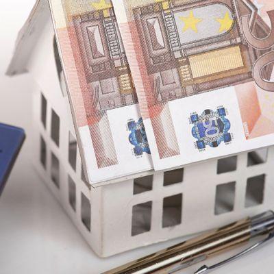 Paperista tehty talo jolla on seteleistä tehty katto, kynä ja laskin.