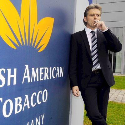 Mies tupakoi British american Tobaccon kyltin vieressä.