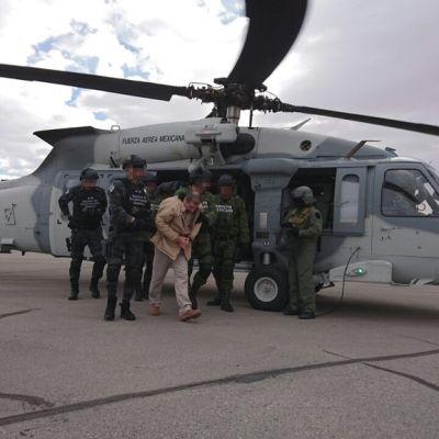 Joukko tummanvihreissä univormuissa olevia turvallisuusviranomaisia kuljettaa käsiraudoissa olevaa miestä helikoperista lentokentällä.