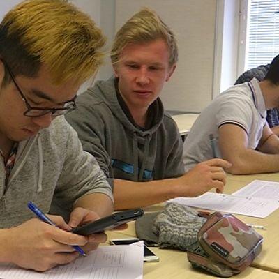 Aasialainen nuori mies käyttää älypuhelinta