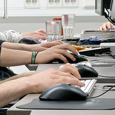 Asiakaspalvelijoita tietokoneiden ääressä.