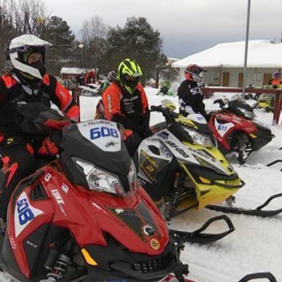 Kolme Giant-moottorikelkkanendurokisassa kilpailevaa moottorikelkkailijaa istuvat kelkkojensa päällä Kemijärven lumisissa maisemissa.