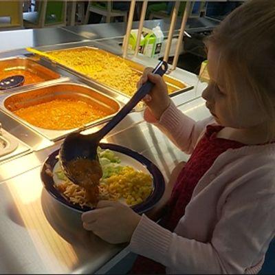 Lapsi ottaa ruokaa.