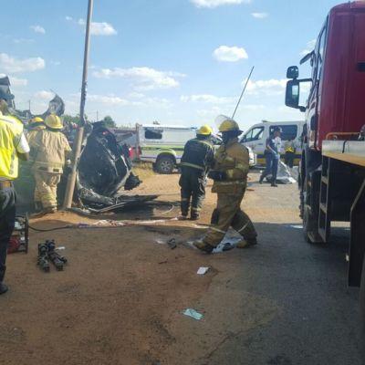 Joukko palokuntalaisia ja muita pelastustyöntekijöitä kolaripaikalla. Vasemmalla näkyy vielä savuavia autoja. Kuvan oikeassa laidassa on punainen paloauto.