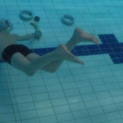 Uppokiekon pelaaja tekee maalin veden alla.