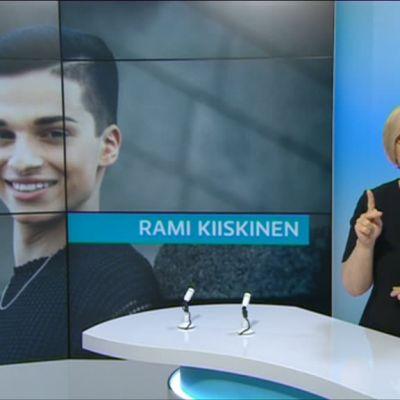 Kuvakaappaus lähetyksestä. Mikaela Tillander viittoo, taustakuvassa Mr Gay Finland -ehdokas Rami Kiiskinen.