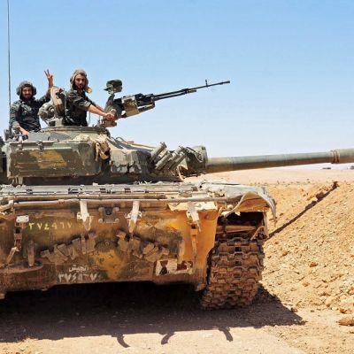 Panssarivaunu erämaamaisemassa. Vaunun tykki osoittaa kuvan oikeaan laitaan. Tykkitornissa näkyy kaksi miestä, toinen seisoo konekiväärin takana, toinen näyttää kädellään voitonmerkkiä.