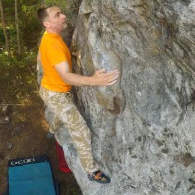 Keltapaitainen mies kiipeää isoa lohkaretta ylöspäin