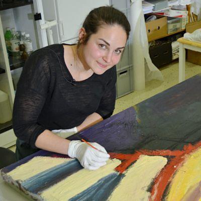 Maalauskonservaattori Veera Lopez-Lehto konservoi Hannu Lukinin maalausta.