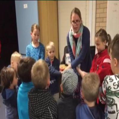 Joukko lapsia ja opettaja seisoo piirissä käsikkäin.