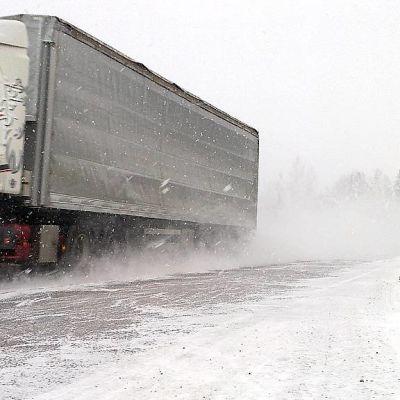 Rekka ajaa tiellä lumisateessa.