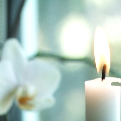 Kynttilä palaa ikkunan edessä. Taustalla kukkasia.