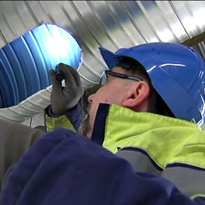 Huoltomies tarkastaa ilmastointiputkia.