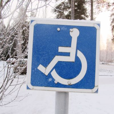Kuvassa invaliidipaikkaa tarkoittava kyltti.