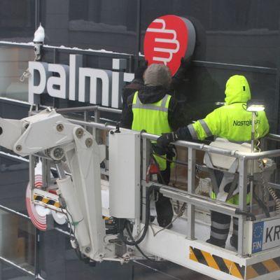Kaksi työntekijää ripustaa Palmian logoa seinälle nostokorista