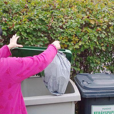 Kuvassa nainen nostaa roskapussia laatikkoon.  taustalla pensasaita