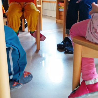 Lasten jalkoja pöydän alla.