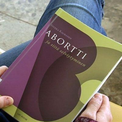 Nuori nainen pitää käsissään aborttia käsittelevää kirjaa.