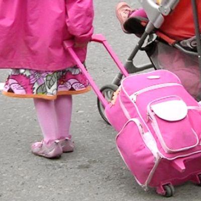 Lapsi vetää matkalaukkua perässään.
