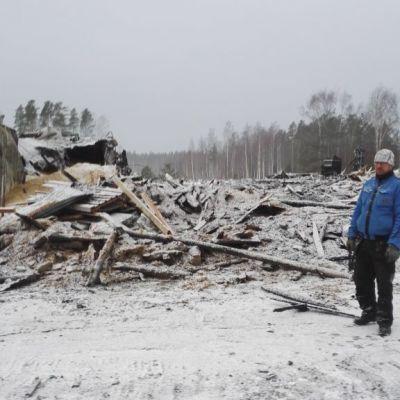 Mies seisoo palaneen sikalarakennuksen raunioiden edessä.