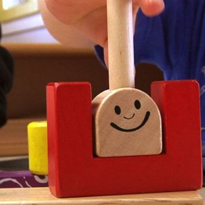 Pöydän alla on puinen hymynaama.