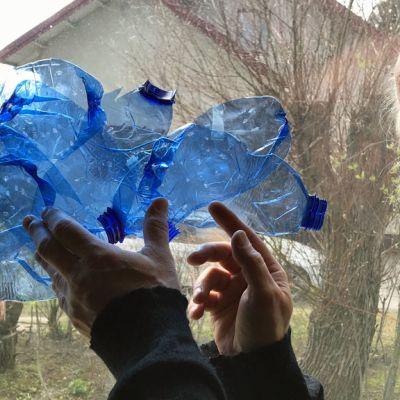 Mies seisoo ikkunan edessä ja pitää käsissään sinisiä muovipulloja.