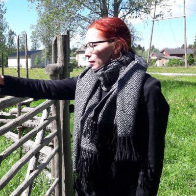 Nainen avaa portin salpaa