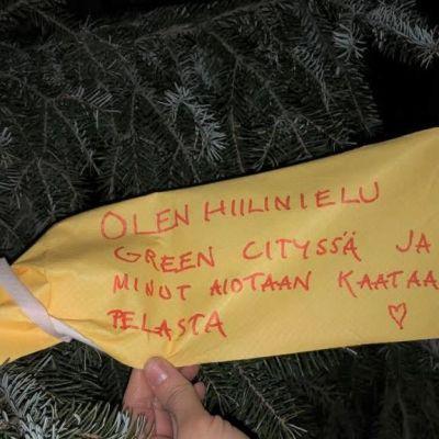 Puuhun kiinnitetty lappu, johon on kirjoitettu, että puu pitäisi pelastaa, koska se on hiilinielu.