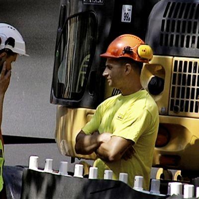 Työmiehet pitävät taukoa. Toinen nuorista miehistä puhuu kännykkään.