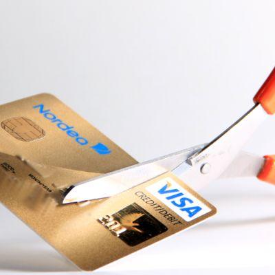 Kuvassa luottokorttia leikataan saksilla.