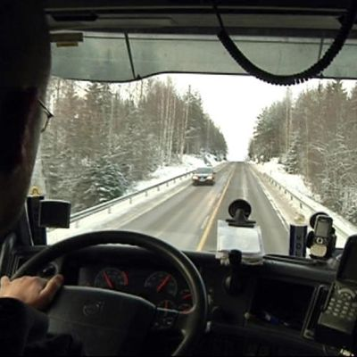 Mies ajaa rekkaa talvisella tiellä.