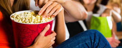 En kvinna håller i en enorm popcornkartong i en biosalong.
