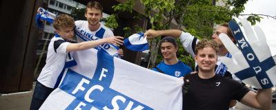 Fem glada unga män håller upp finska flaggor och fotbollshalsdukar