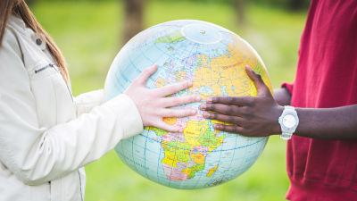Två par händer håller i en jordglob.